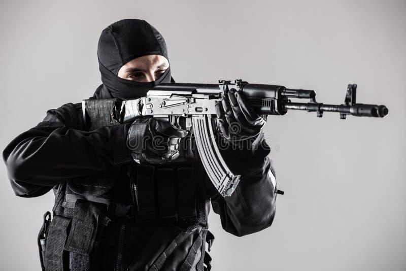 Soldatmann-Griff Maschinengewehr der besonderen Kräfte auf einem grauen Hintergrund lizenzfreie stockfotos