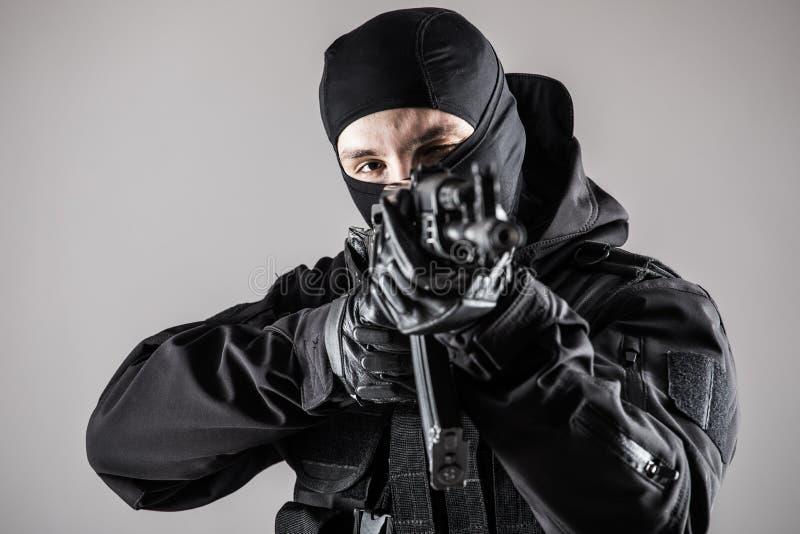Soldatmann-Griff Maschinengewehr der besonderen Kräfte auf einem grauen Hintergrund lizenzfreie stockbilder