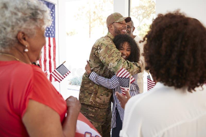 Soldato afroamericano millenario che abbraccia la sua famiglia dopo la restituzione della casa, fine su, fuoco selettivo immagine stock