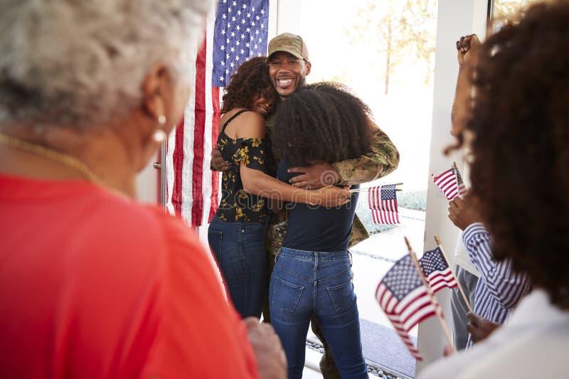 Soldato afroamericano millenario che abbraccia la sua famiglia dopo la restituzione della casa, fine su, sopra la vista della spa fotografia stock