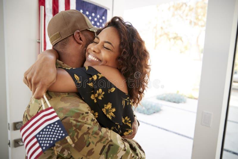 Soldato afroamericano millenario che abbraccia la sua moglie dopo essere arrivato di nuovo a casa, fine su fotografia stock