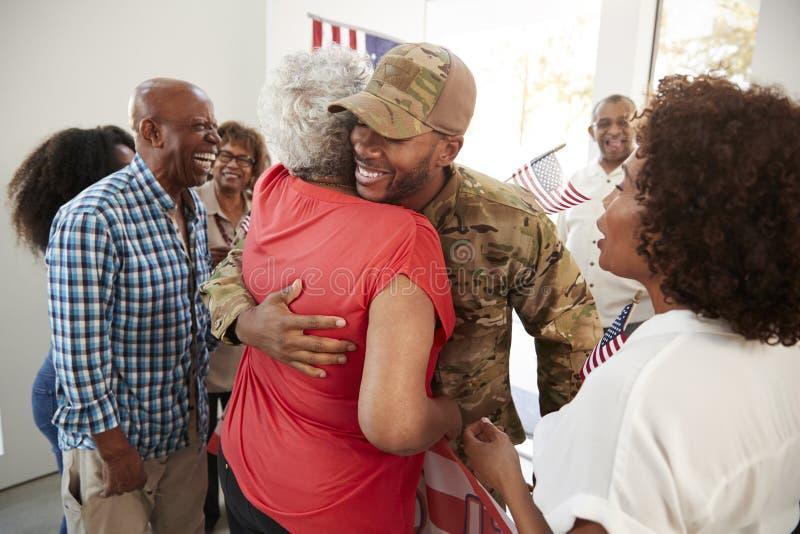 Soldato afroamericano millenario che ritorna a casa alla famiglia che abbraccia sua nonna, fine su immagine stock libera da diritti