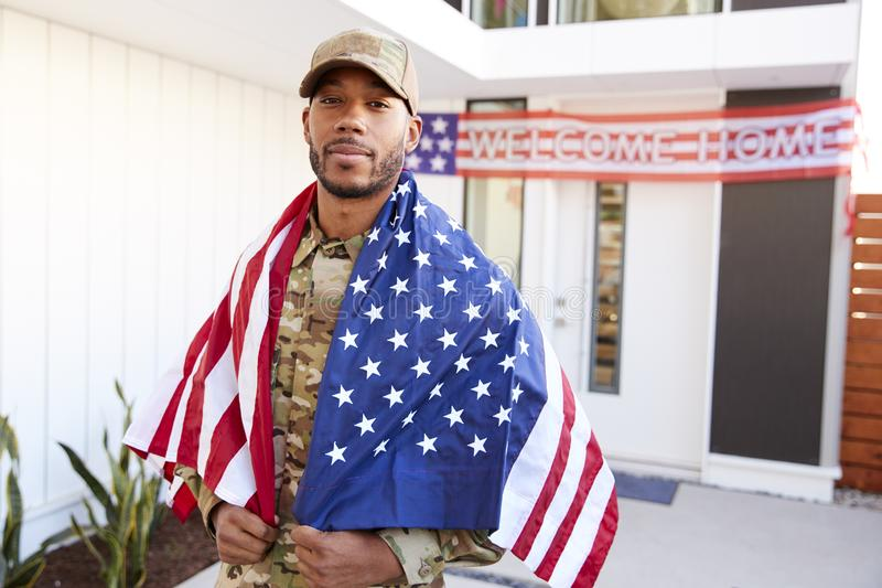 Soldato afroamericano millenario con la bandiera degli Stati Uniti coperta sopra le sue spalle, guardanti alla macchina fotografi fotografia stock