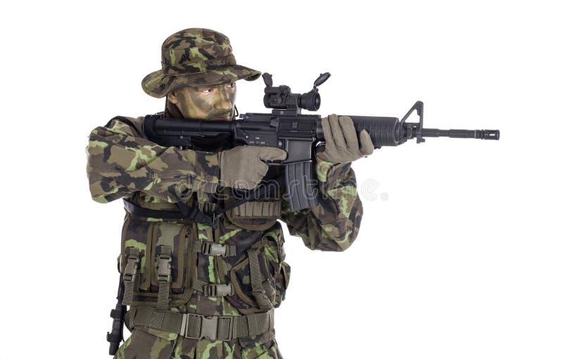 Soldato in cammuffamento ed arma moderna M4 immagine stock