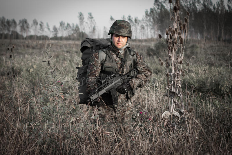 Soldato con il casco militare e pistola in regione selvaggia immagini stock