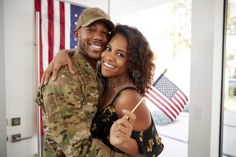 Soldato millenario e moglie afroamericani che abbracciano a casa e che sorridono alla macchina fotografica, bandiera d'ondeggiame immagini stock