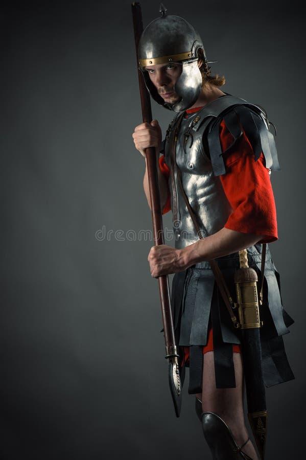Soldato romano in armatura con una lancia a disposizione fotografia stock libera da diritti