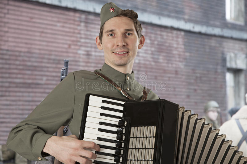 Soldato sovietico che gioca la fisarmonica all'aperto fotografia stock