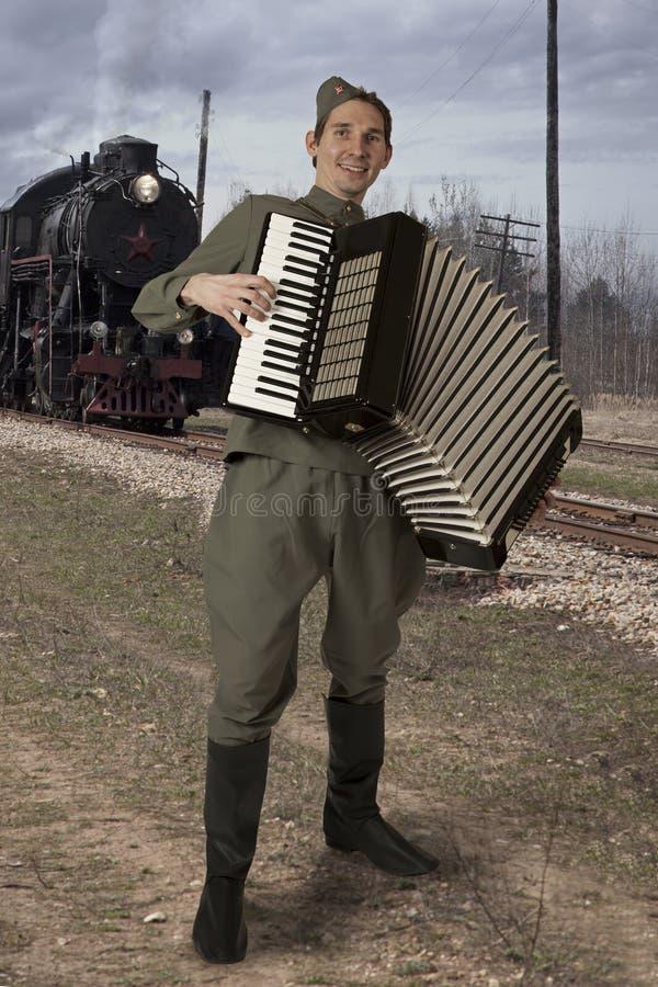 Soldato sovietico con una fisarmonica all'aperto fotografia stock libera da diritti