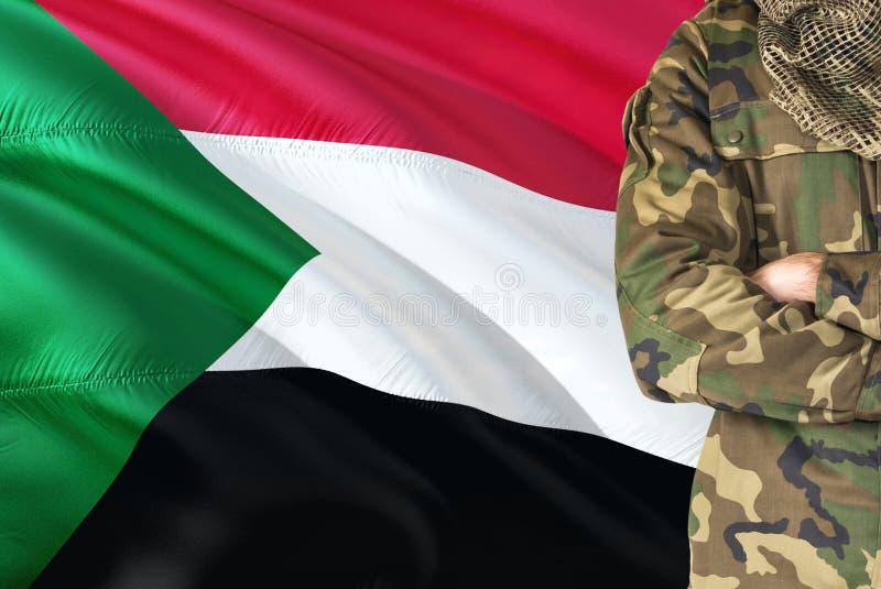 Soldato sudanese attraversato di armi con la bandiera d'ondeggiamento nazionale su fondo - tema militare del Sudan immagine stock