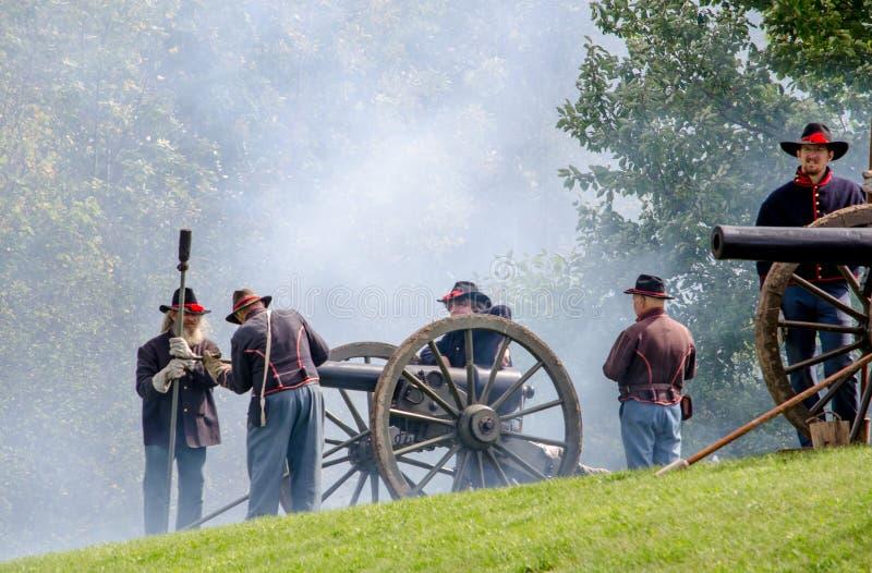 Soldats confédérés mettant le feu outre des canons photographie stock