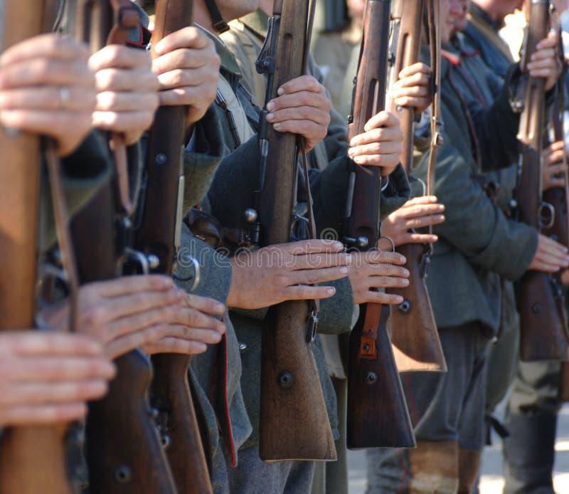 Soldats dans des bras photos stock