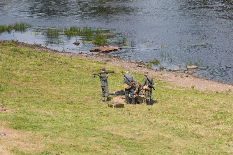 Soldats dans l'uniforme allemand, avec des armes, sur la berge, de derrière du photos stock