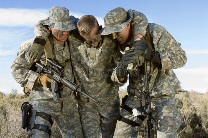 Soldats dans le collègue de transport de champ photos stock