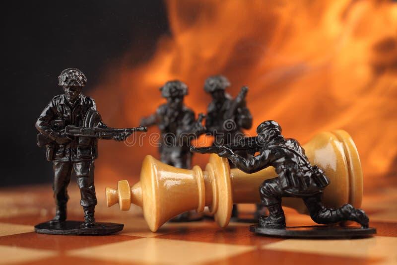 Soldats de jouet combattant le roi d'échecs image stock