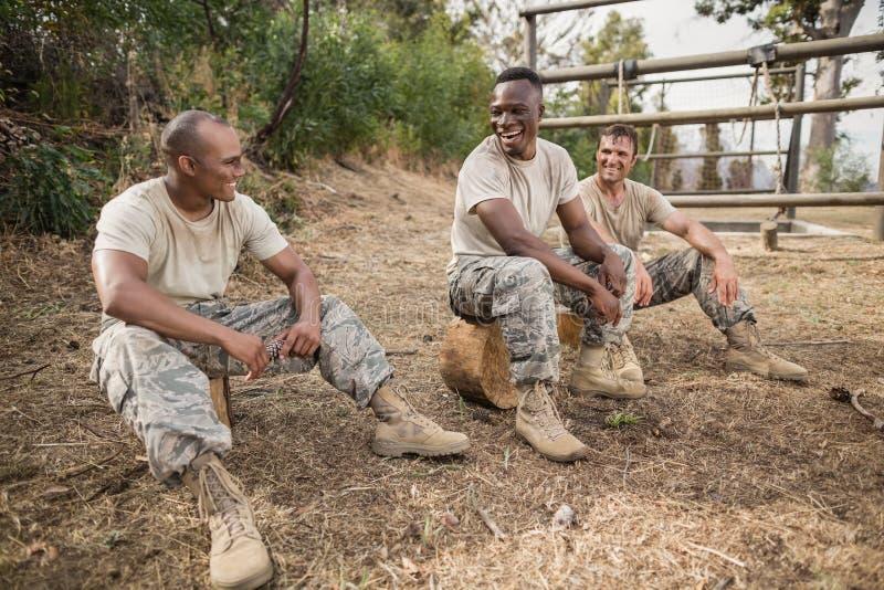 Soldats militaires agissant l'un sur l'autre pendant la formation d'obstacle photographie stock