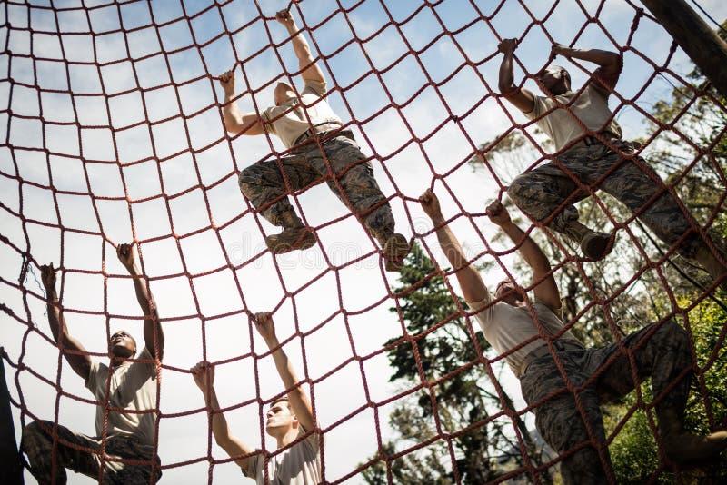 Soldats militaires montant la corde pendant le parcours du combattant photos stock