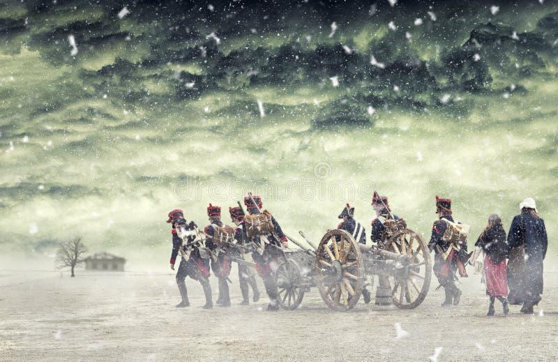 Soldats napoléoniens et femmes marchant dans la neige en baisse et tirant un canon dans la terre simple, campagne avec les nuages images stock