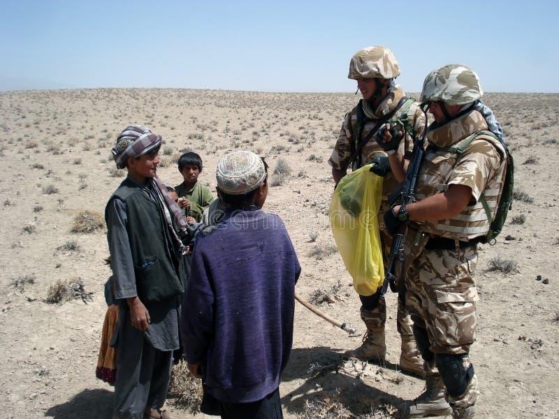 Soldats partageant la nourriture en Afghanistan images libres de droits
