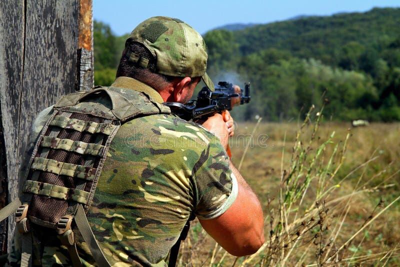 Soldatschießen mit Kalaschnikowsturmgewehr lizenzfreie stockfotos