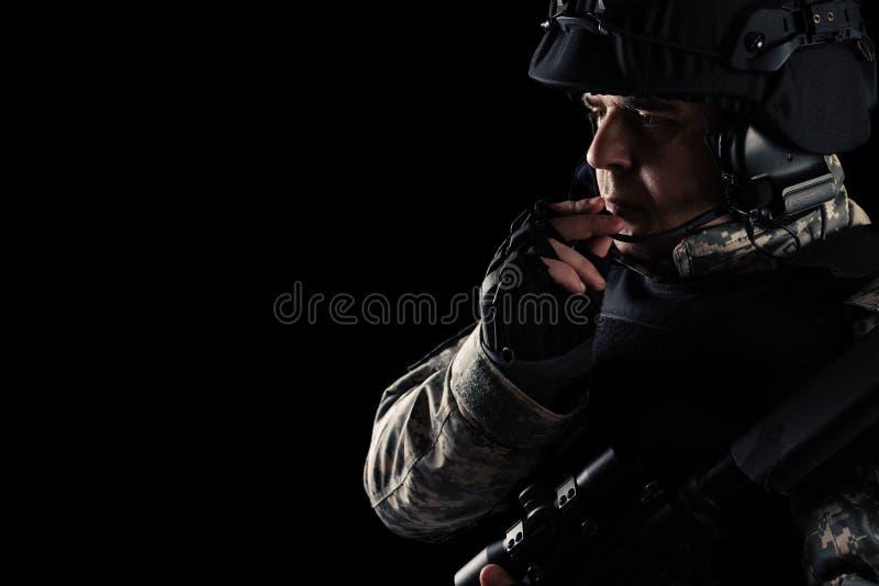 Soldatspecialf?rband med gev?ret p? m?rk bakgrund arkivbild