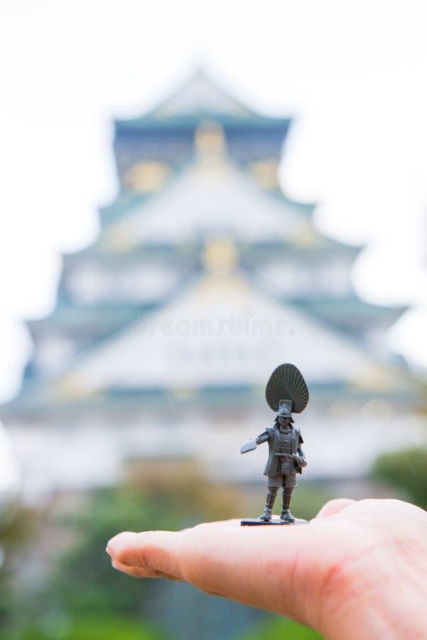 Soldatspielzeug an Hand mit unscharfem Osaka Castle als Hintergrund lizenzfreie stockbilder