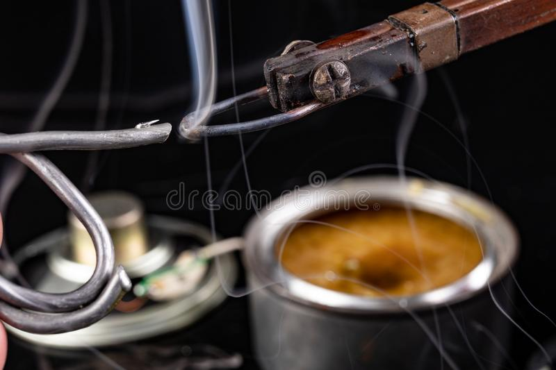 Soldering of an integrated circuit in an electronics workshop. Small electronic works. Dark background, chip, component, computer, connection, detail, device royalty free stock photo