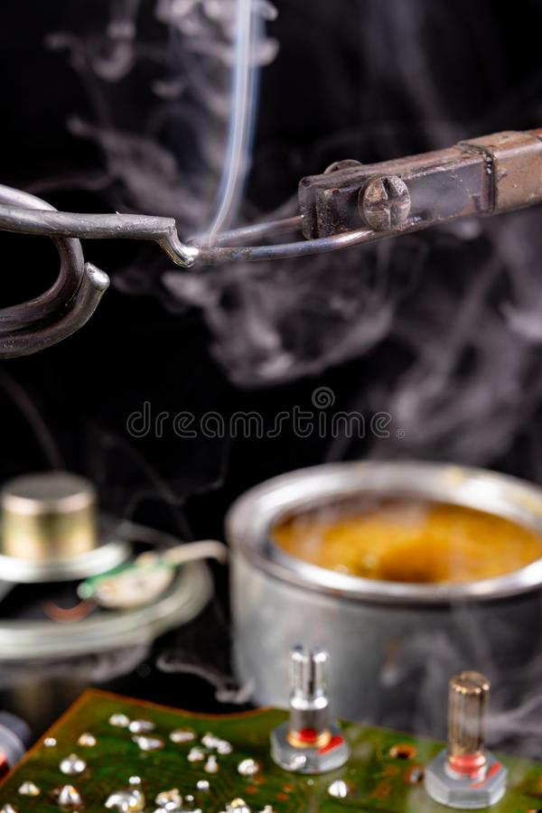 Soldering of an integrated circuit in an electronics workshop. Small electronic works. Dark background, chip, component, computer, connection, detail, device stock photos