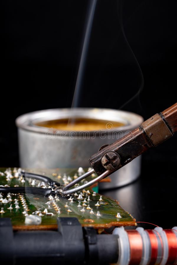Soldering of an integrated circuit in an electronics workshop. Small electronic works. Dark background, chip, component, computer, connection, detail, device royalty free stock image