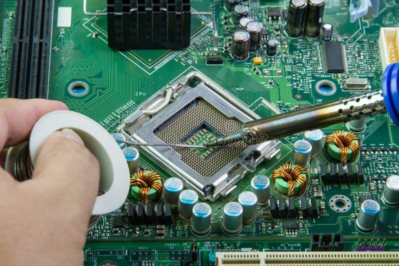 Soldering iron and microcircuit.Computer motherboard repair stock photos