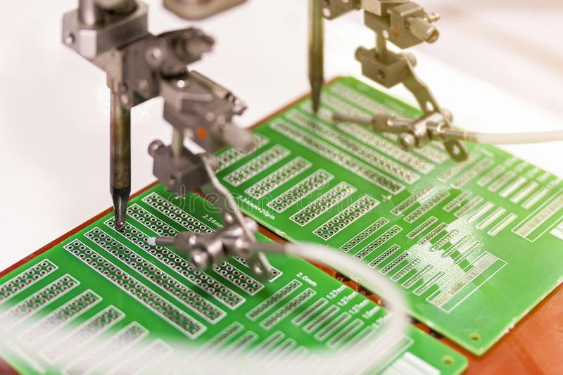 Soldering iron tips of automated manufacturing soldering and assembly printed electric circuit board PCB.  stock photos