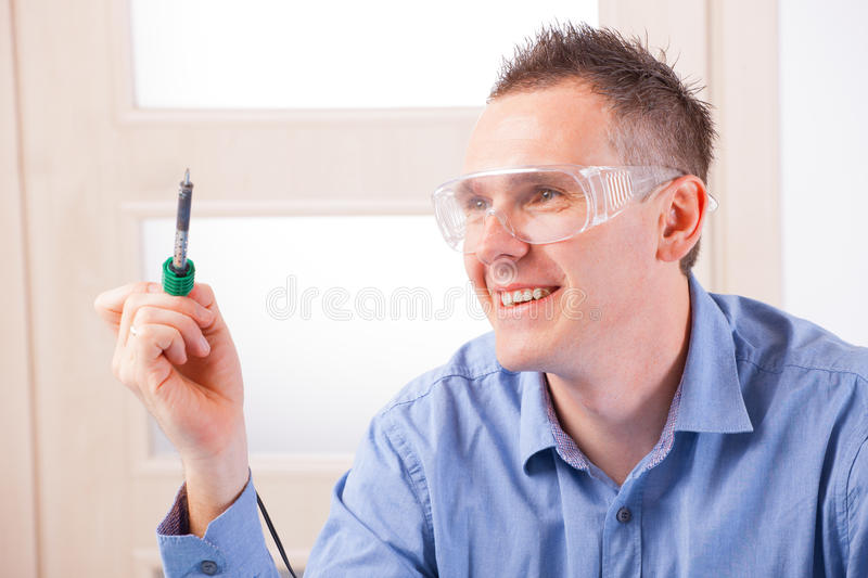 Soldering. Man using soldering tool wearing safety glasses stock images