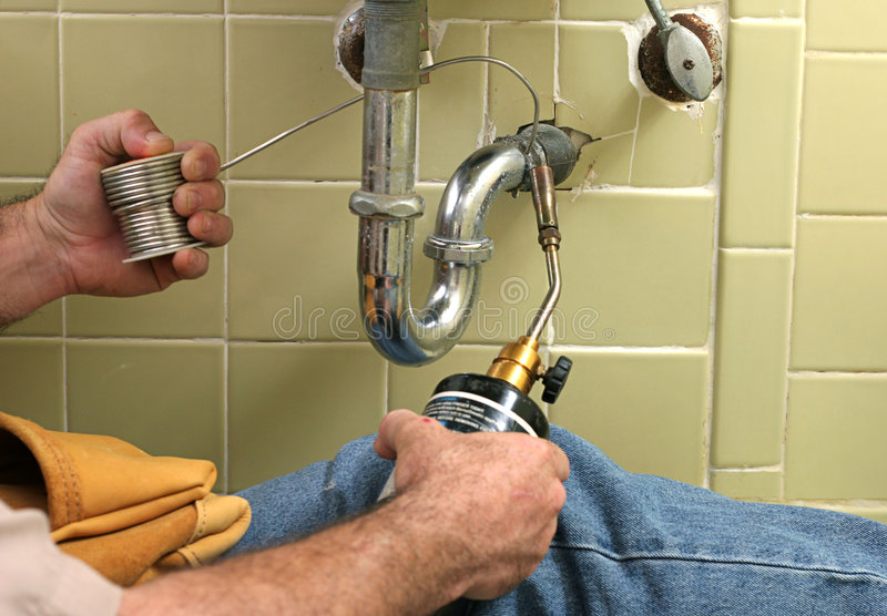 Soldering Pipe. A plumber using a welding torch to solder pipe royalty free stock photos