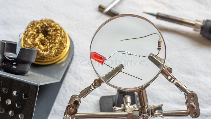 Soldering a resistor and LED with a magnifying glass, with alligator clips holding the components stock photography