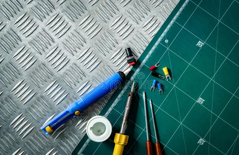 Soldering tools. Soldering iron, spool of soldering wire, screwdriver, solderless insulated spade terminals put on industrial royalty free stock photos