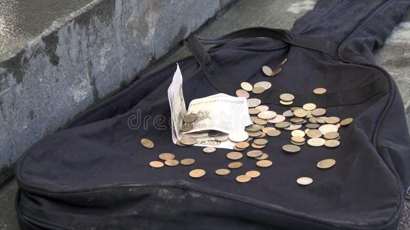 Soldi che cadono sulla cassa nera della chitarra sul marciapiede all'aperto della città Chiuda su per biglietto e le monete che s fotografie stock libere da diritti