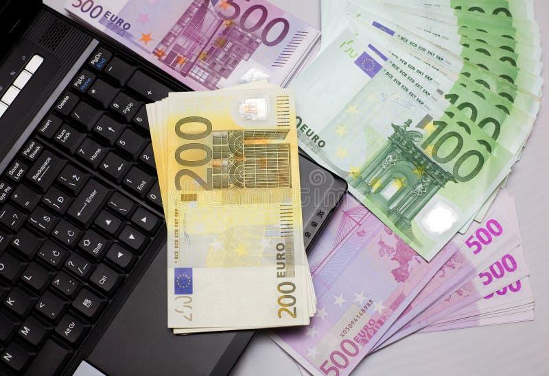 Soldi contro l'euro del computer portatile contro il taccuino immagine stock