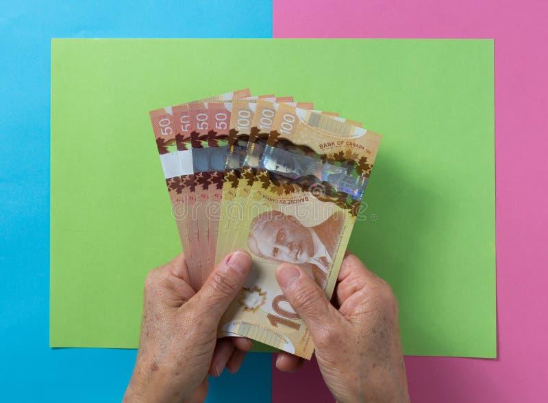 Soldi dal Canada Dollari Vista superiore della mano del ` s della donna anziana che tratta le fatture fotografia stock