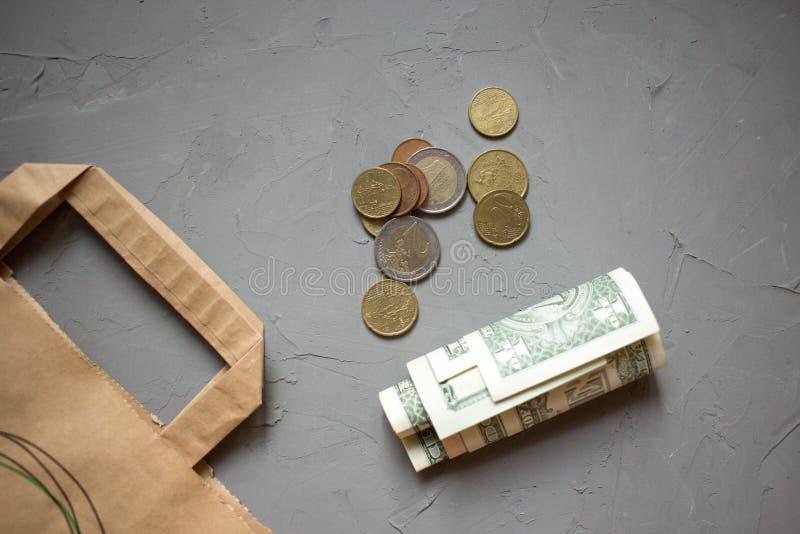 Soldi dei dollari dei contanti, euro monete con un pacchetto di Kraft su grigio fotografia stock