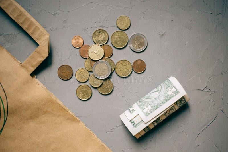 Soldi dei dollari dei contanti, euro monete con un pacchetto di Kraft su grigio fotografia stock libera da diritti