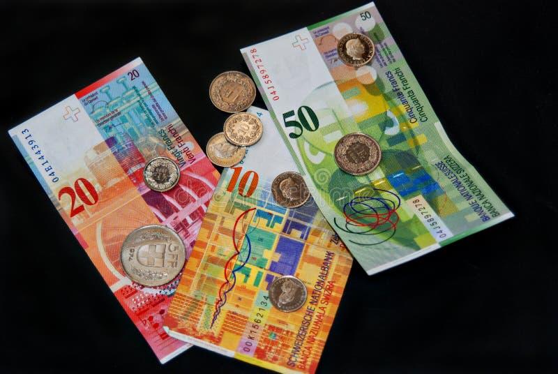 Soldi del franco svizzero sul nero, sulle monete e sulle banconote fotografie stock