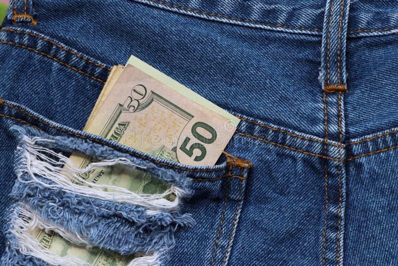 Soldi della banconota cinquanta dollari americani nella tasca posteriore delle blue jeans fotografia stock