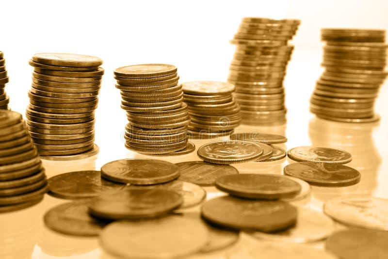 Soldi della moneta in pile di toni dell'oro immagine stock