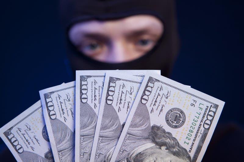 Soldi della tenuta del ladro isolati su blu scuro fotografia stock libera da diritti