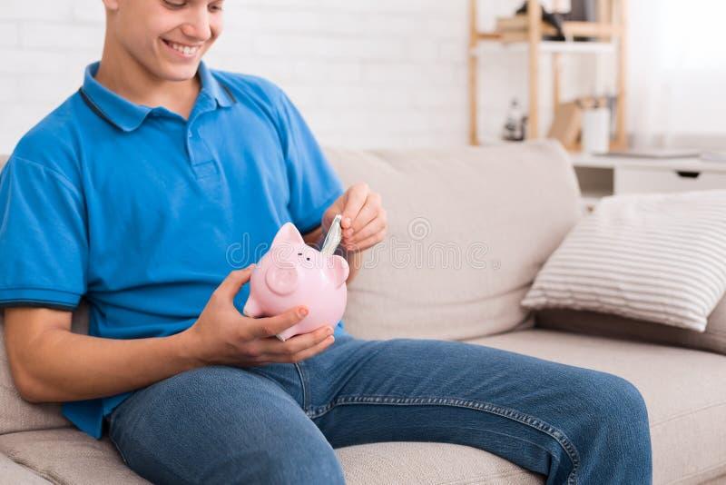 Soldi di risparmio del tipo teenager con il porcellino salvadanaio immagini stock libere da diritti