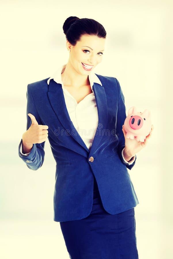 Soldi di risparmio della donna di affari in un piggybank fotografia stock
