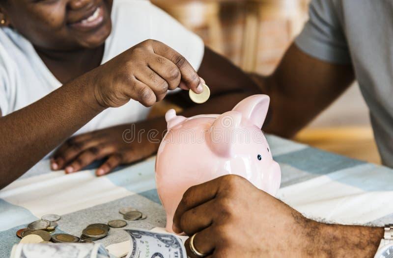 Soldi di risparmio della figlia e del papà al porcellino salvadanaio immagine stock libera da diritti