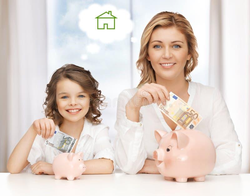Soldi di risparmio della figlia e della madre fotografie stock