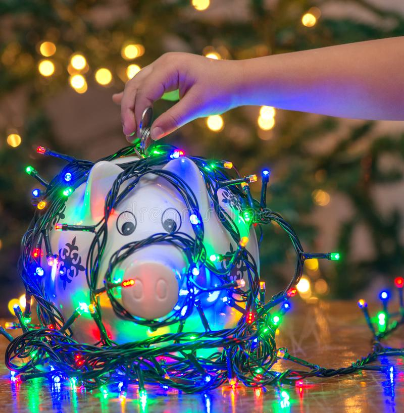 Soldi di risparmio della mano del bambino per i regali di Natale fotografia stock libera da diritti