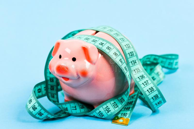 Soldi di risparmio porcellino salvadanaio con nastro adesivo di misura moneybox dieta dei soldi Finanza e commercio Concetto di p immagini stock libere da diritti